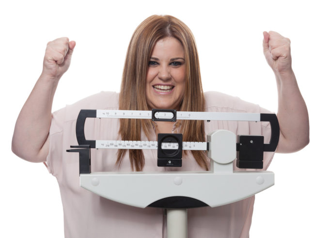 Smiling woman raising arms on a medical weight scale. White background.